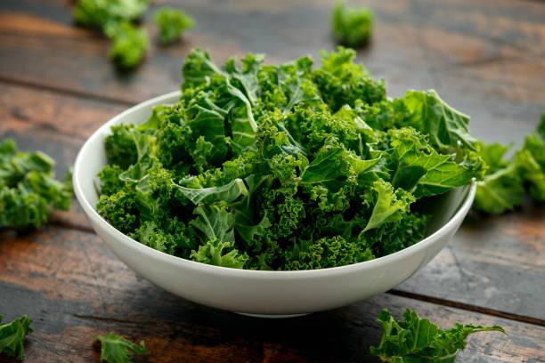 Raw Organic Kale in white bowl on wooden table stock photo