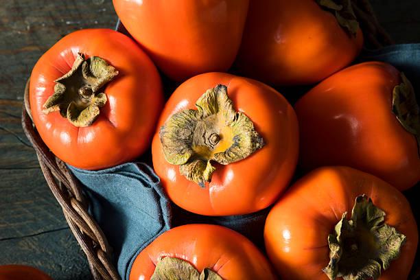 raw organic orange perssimons - sharonfrucht stock-fotos und bilder