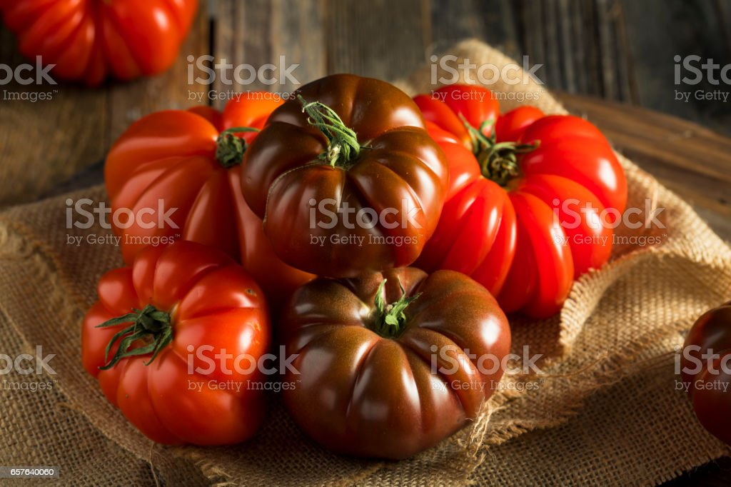 Raw Organic Red and Brown Heirloom Tomatoes stock photo