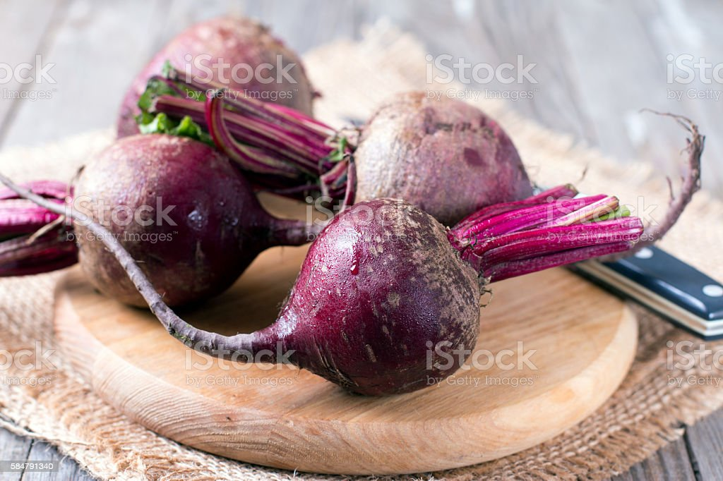 Raw organic red beets on wooden table stock photo