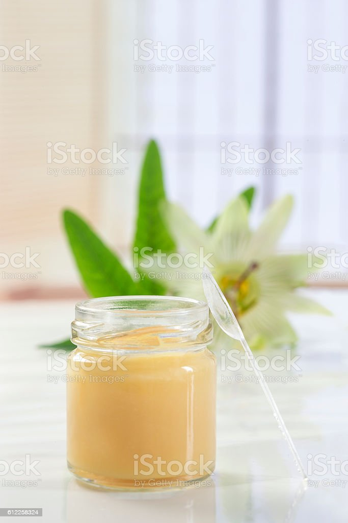 raw organic royal jelly in a small bottle with passiflora stock photo