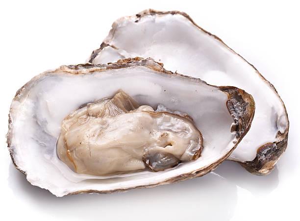 raw oyster and lemon on a whte background. - schaaldier stockfoto's en -beelden