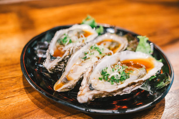 3 raw oyster freshly opened and served on dish at japanese restaurant. fresh seafood famous menu. healthy eating concept - oyster stock pictures, royalty-free photos & images