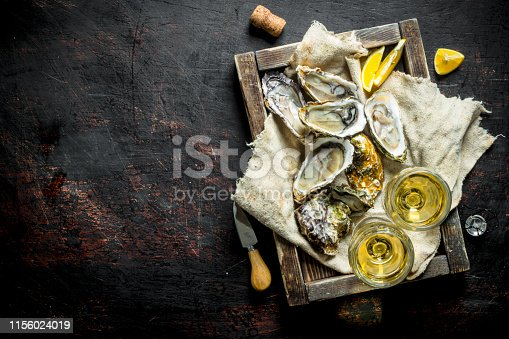 Raw oysters on a rag in a wooden tray with glasses of white wine. On dark rustic background