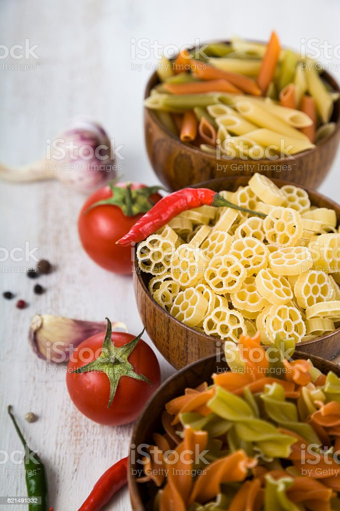Raw pasta and spices in wooden bowls photo libre de droits