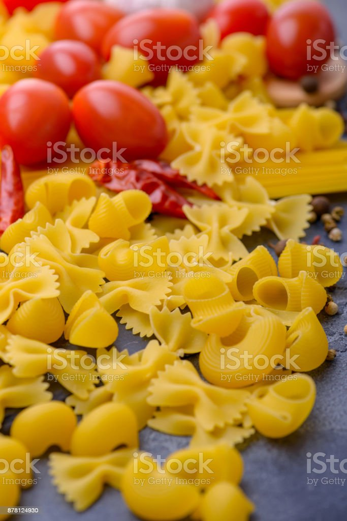 Raw pasta and tomatoes. Ingredients for cooking stock photo