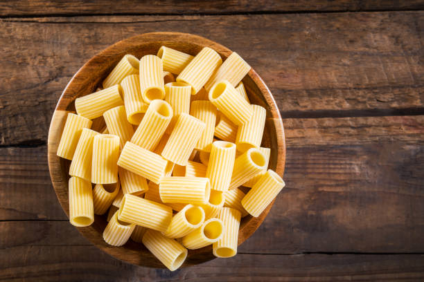 Raw Pasta  Mezzi Rigatoni in Wooden Bowl Raw Pasta  Mezzi Rigatoni in Wooden Bowl on Dark Rustic Background rigatoni stock pictures, royalty-free photos & images
