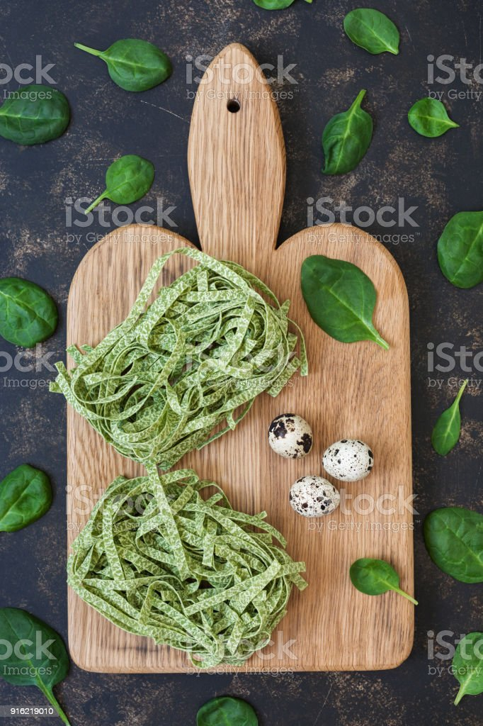 Raw pasta nests with spinach on a dark background. stock photo