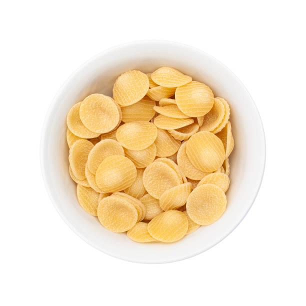 Raw pasta orecchiette in white small bowl. Isolated Raw pasta orecchiette in white small bowl. Isolated orecchiette stock pictures, royalty-free photos & images