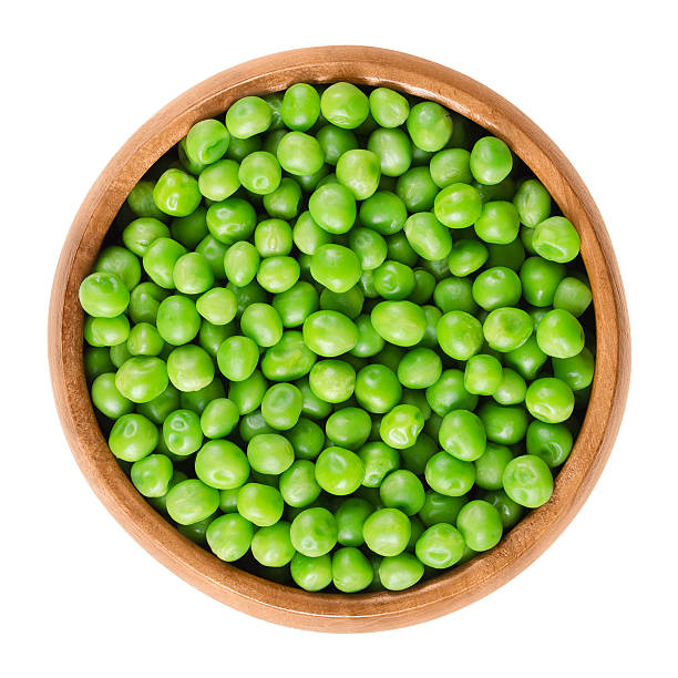 Raw peas in wooden bowl over white stock photo