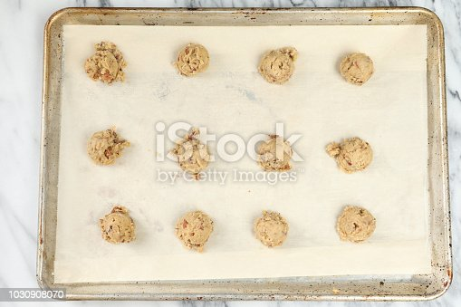 An overhead horizontal photograph of a baking pan  with a dozen raw pecan cookies.