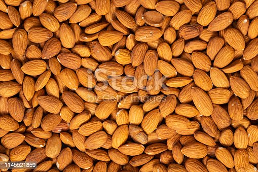 Food texture background of big raw peeled almonds , top view.