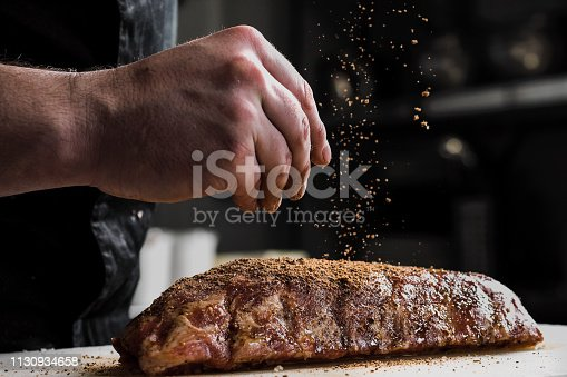 Raw piece of meat, beef ribs. The hand of a male chef puts salt and spices on a dark background, close-up.