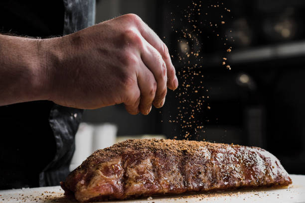 raw piece of meat, beef ribs. the hand of a male chef puts salt and spices on a dark background. - meat imagens e fotografias de stock
