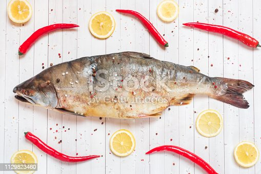 istock Raw pink salmon fish with spices, lemon and chili pepper on a light table. 1129823460