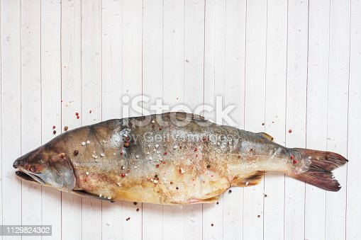 istock Raw pink salmon fish with spices on a light table. Copy space 1129824302