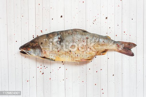 istock Raw pink salmon fish with spices on a light table. 1129824301