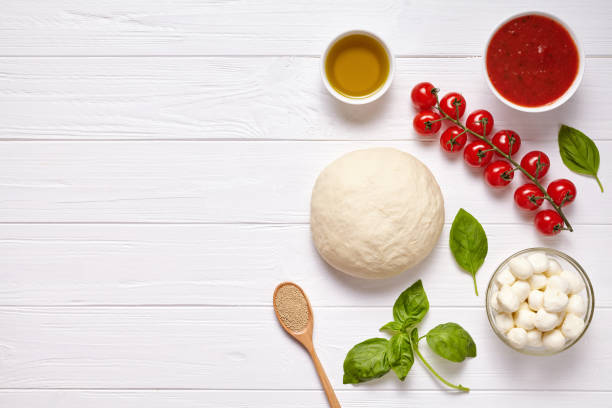 Raw pizza dough with baking ingredients: mozzarella cheese, tomatoes sauce, basil, olive oil, cheese, spices. Italian margherita on wooden table. Italian pizza margarita stock photo