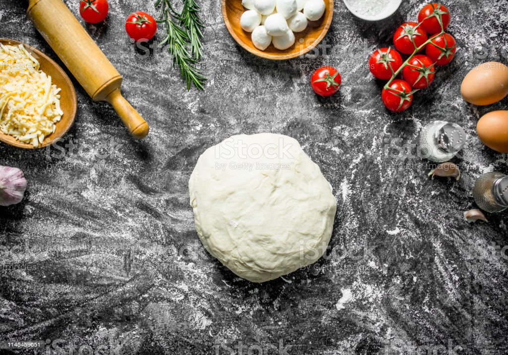 Raw pizza. Dough with different ingredients for cooking homemade...