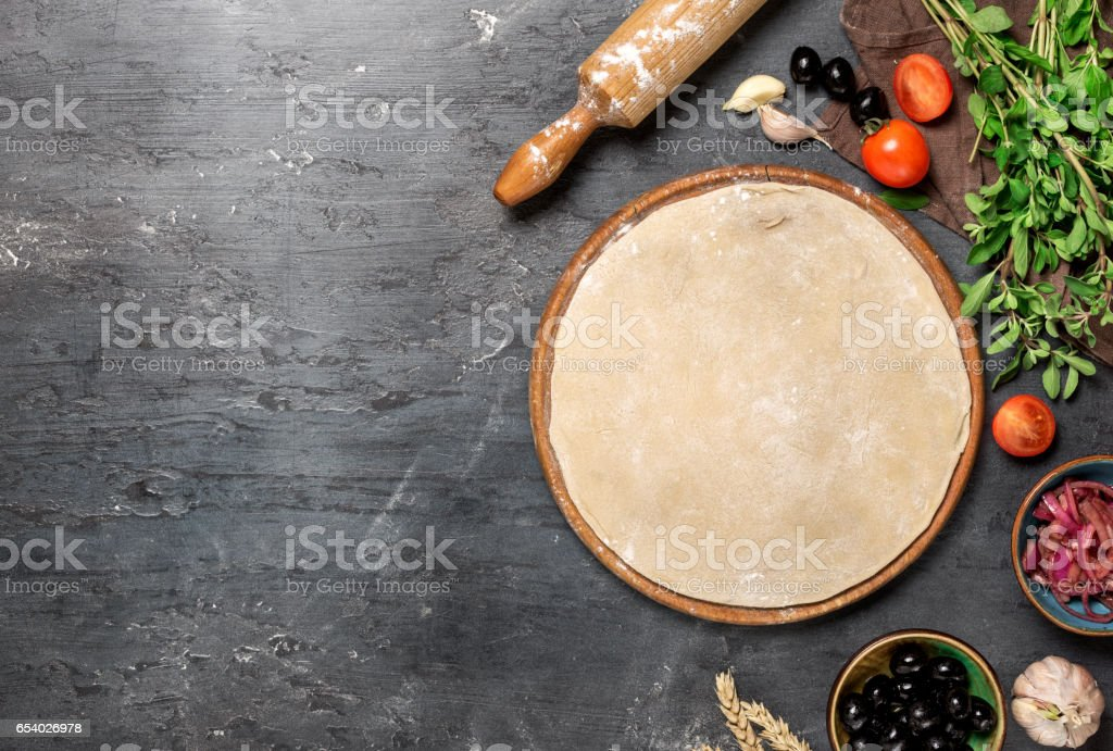 Raw pizza dough with ingredients for cooking vegetarian pizza on the dark stone surface with border, top view stock photo