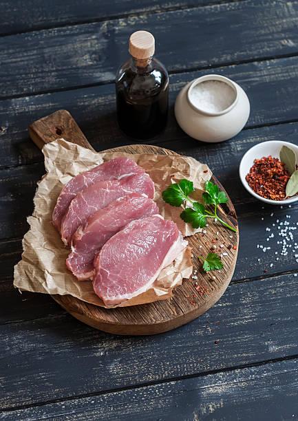 roh schweinefleisch-koteletts und gewürzen auf einem rustikalen schneidebrett - paprikaschnitzel stock-fotos und bilder