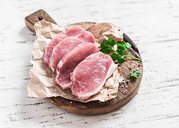 roh schweinekoteletts auf rustikalen holz schneidebrett - paprikaschnitzel stock-fotos und bilder