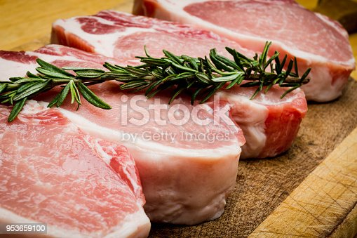 Thick raw pork chops ready to be grilled