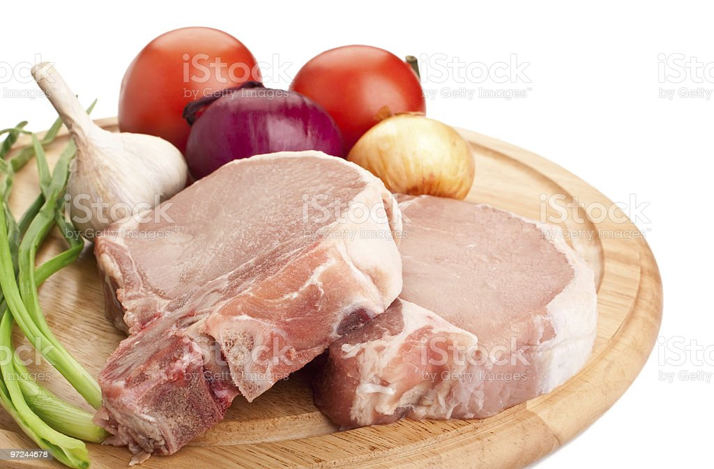 Raw pork chops with vegetables on wooden circle board royalty-free stock photo