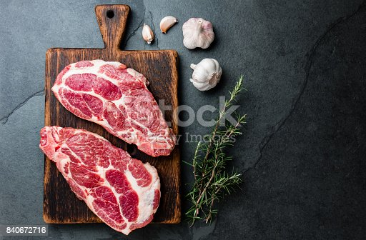 istock Raw pork cutlet chop for grill BBQ with herbs on wooden board, slate background, top view, copy spaces 840672716