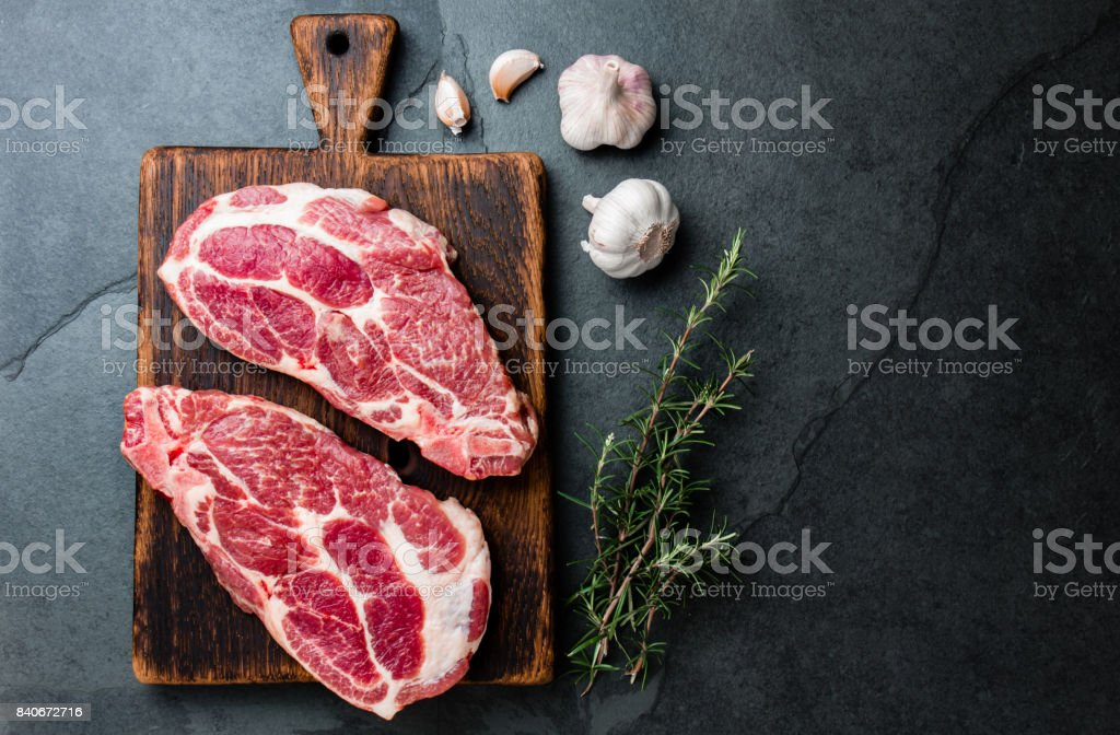 Raw pork cutlet chop for grill BBQ with herbs on wooden board, slate background, top view, copy spaces stock photo