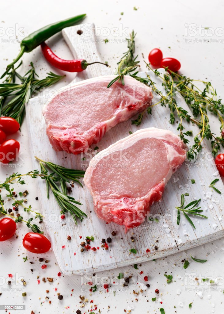 Raw Pork Loin chops on a cutting board with herbs, rosemary, thyme, chilli, salt, pepper on white cutting board. foto stock royalty-free