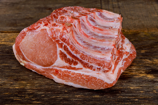 Raw pork meat on ribs isolated on wooden background.