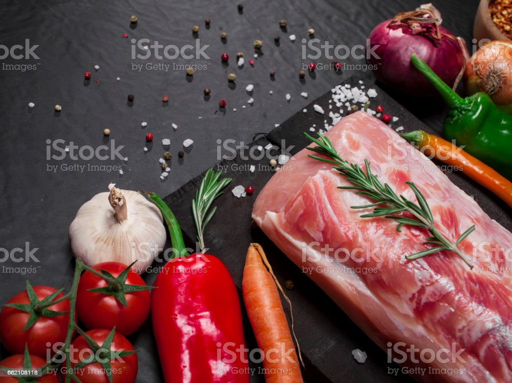Raw pork meat on a cutting board with rosemary, vegetables and spices. royalty-free stock photo