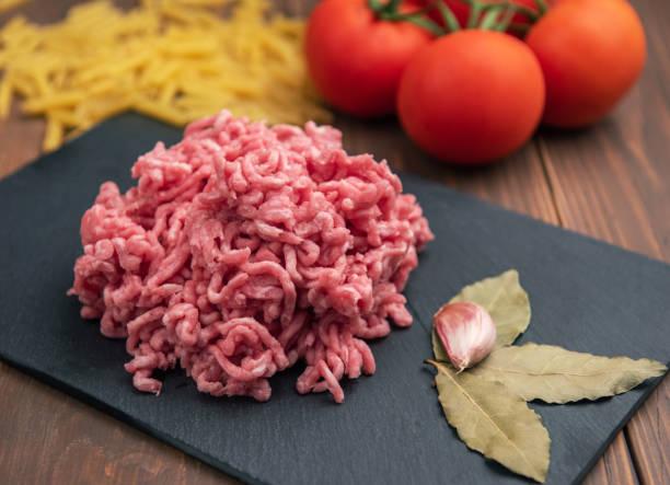Rohes Schweinefleisch auf schwarzem Teller und Holzhintergrund – Foto
