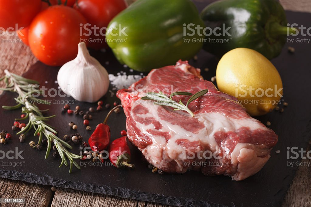 raw pork neck and vegetables close-up on board. horizontal stock photo