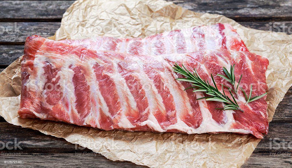 Raw Pork ribs with a rosemary. on crumpled paper stock photo