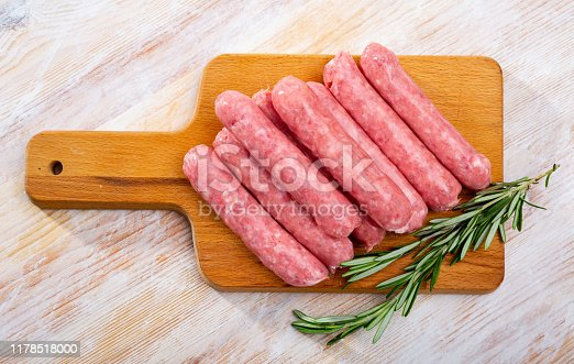 Traditional Catalan raw pork sausage botifarra ready for grilling on wooden board