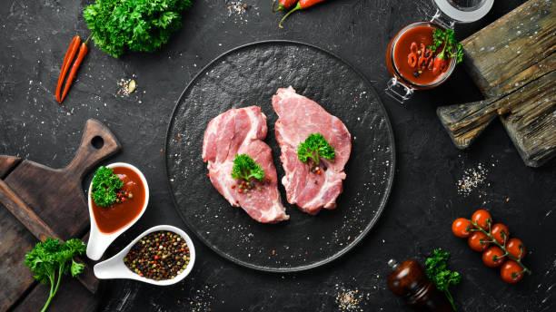 Bife de porco cru. Carne fresca. Em um prato de especiarias e ervas. Vista superior. Espaço livre para o seu texto. - foto de acervo