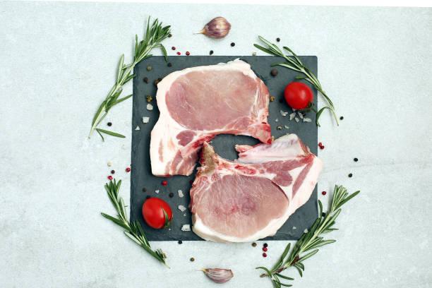 Raw pork steak on bone on light background. stock photo