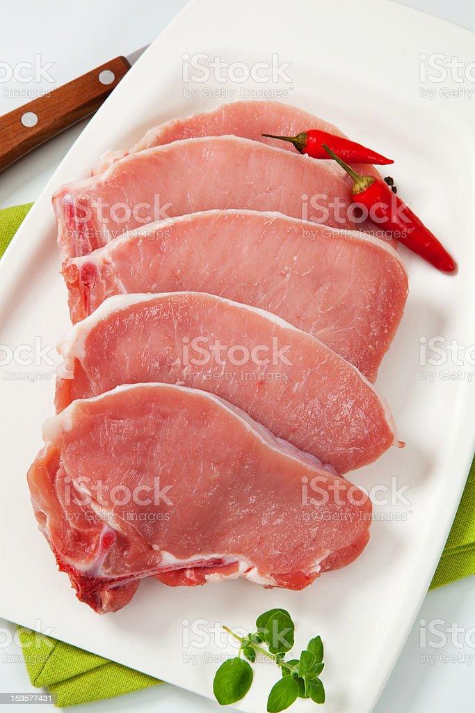 Raw pork steaks garnished, salver, green napkin royalty-free stock photo