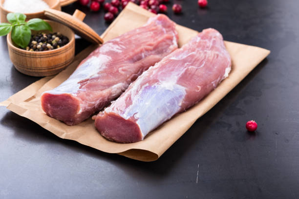 Raw pork tenderloin on craft pape Raw pork tenderloin on craft paper ready to cook pork stock pictures, royalty-free photos & images