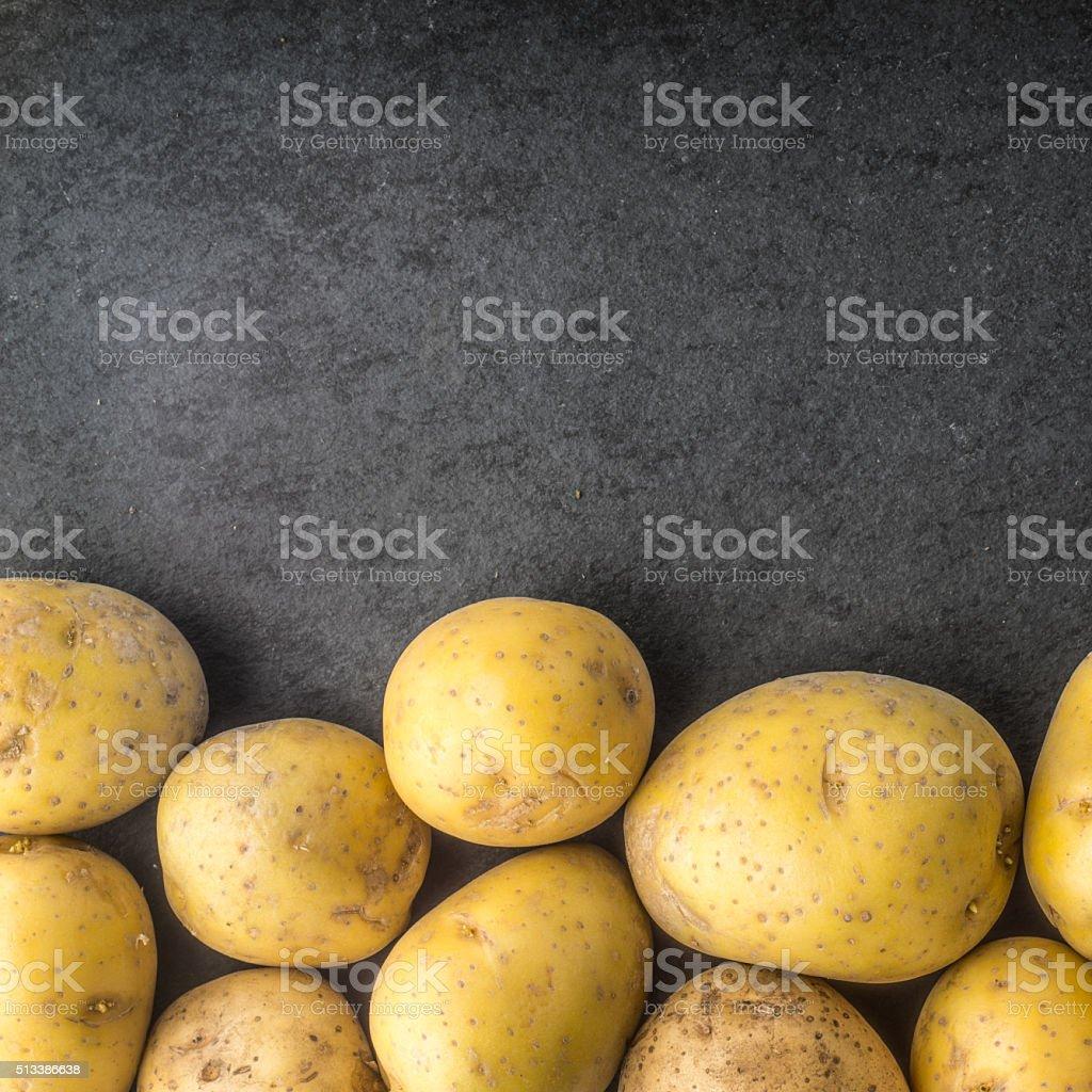Roh Kartoffeln auf den schwarzen Steinen Tisch Platz Lizenzfreies stock-foto
