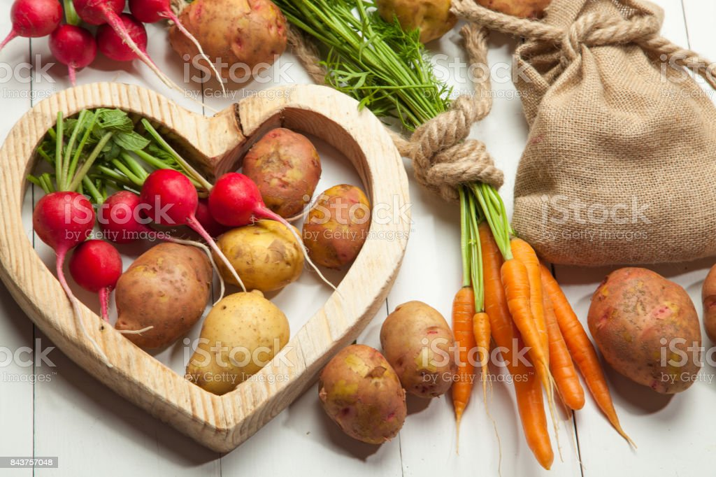 Raw potatoes, radishes and carrots on a white wooden background stock photo