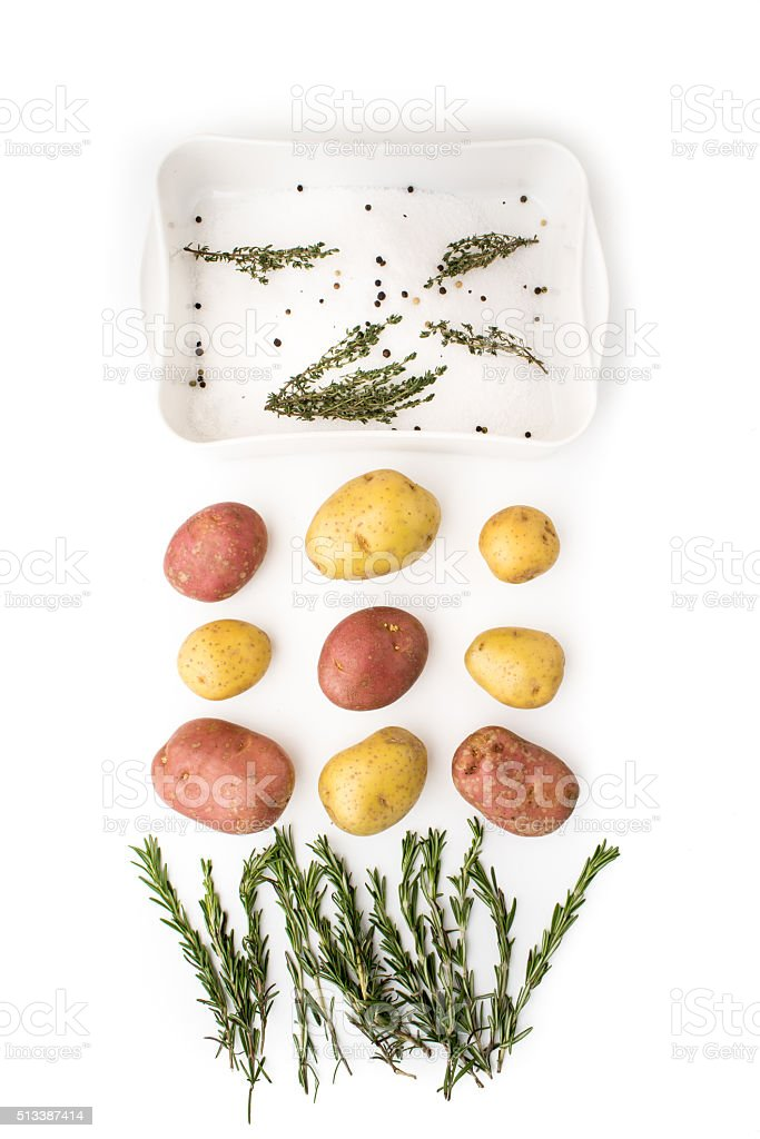 Raw potatoes with spices and herbs on the white background stock photo