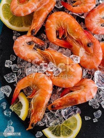 Raw prawns with lemon on ice, close-up