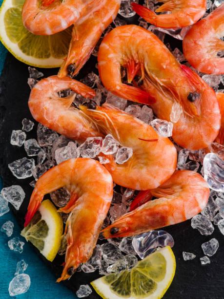 Cтоковое фото Raw prawns with lemon on ice.
