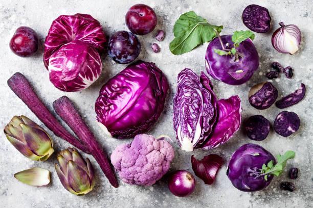 lila rohkost über grauen beton hintergrund. kohl, radicchio-salat, oliven, kohlrabi, karotten, blumenkohl, zwiebeln, artischocken, bohnen, kartoffeln, pflaumen. ansicht von oben flach legen. - lila palette stock-fotos und bilder