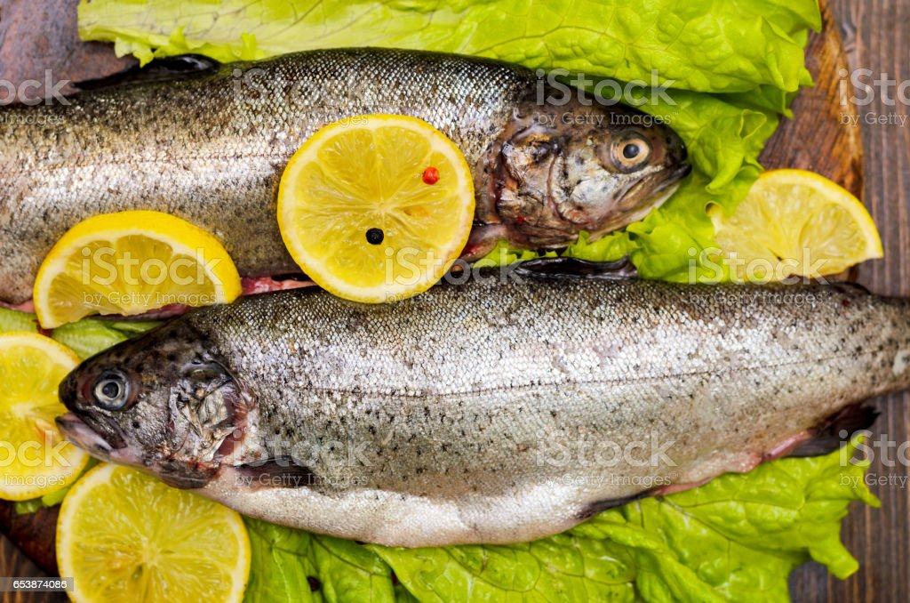 Raw rainbow trout fish on natural black stone background with salad and lemon stock photo