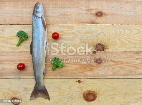 istock Raw rainbow trout river fish on a wooden background with vegetables 1320713933