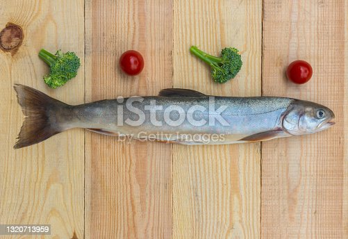 istock Raw rainbow trout river fish on a wooden background with vegetables 1320713959